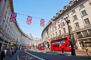 Regents St with red buses and bunting in London street.